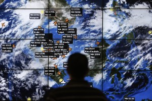 A man watches a large screen showing different flights at the departure hall of Kuala Lumpur International Airport