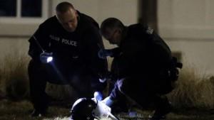 Agenti della polizia di Ferguson che analizzano il luogo della sparatoria