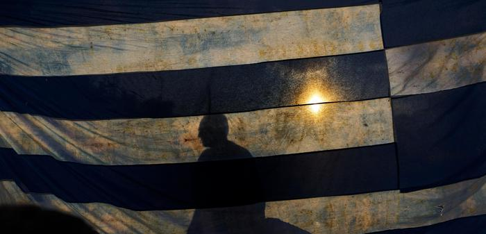 A man is silhouetted as he stands behind a representation of the the Greece national flag, as he takes part in a protest held by supporters of the NO vote in the upcoming referendum, at Syntagma square in Athens on Monday, June 29, 2015. Anxious Greek pensioners swarmed closed bank branches and long lines snaked outside ATMs as Greeks endured the first day of serious controls on their daily economic lives ahead of a July 5 referendum that could determine whether the country has to ditch the euro currency and return to the drachma. (ANSA/AP Photo/Daniel Ochoa de Olza)