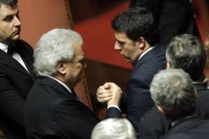Il presidente del Consiglio, Matteo Renzi (D), stringe la mano a Denis Verdini in Senato durante il voto di fiducia al Governo, Roma, 24 febbraio 2014. ANSA/GIUSEPPE LAMI