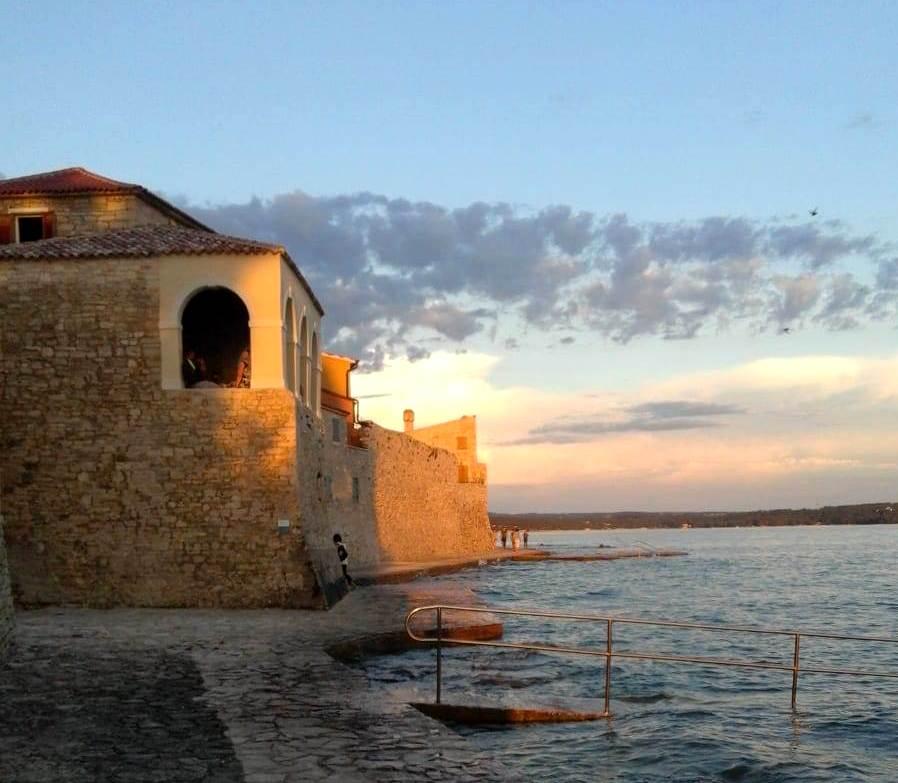 Al tramonto il paese croato di Novigrad si colora di una luce dorata che illumina le mura veneziane del XIII secolo lambite dal mare. Foto di Cinzia  Albertoni