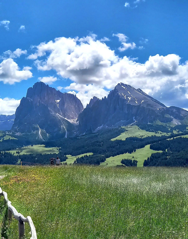 L'Alpe di Siusi è l'altopiano più vasto d'Europa e si estende per 52 kmq a una quota tra i 1800 e 2200 m. a nord-est di Bolzano. Gli Altoatesini  lo proteggono con scrupolosa e giustificata severità, impedendone il traffico automobilistico e la costruzione di nuove case, per cui è punteggiato solo da vecchie baite in legno e da qualche albergo. La strada per raggiungere l'unico parcheggio in località  Compatsch è chiusa dalle 9.00 alle 17.00 perciò per  salirvi  bisogna utilizzare l'autobus dai paesi sottostanti di Fiè, Siusi o Castelrotto o la veloce cabinovia che in 13 minuti sale da Siusi al Compatsch.  L'Altopiano è uno spettacolo in tutte le stagioni e lo si può attraversare a piedi, in bicicletta, con gli sci d'inverno o con la carrozza trainata da tranquillissimi cavalli.  Nella foto il Sassolungo, un gigantesco faraglione roccioso alto 3181m. e il Sasso Piatto,  una piramide irregolare di dura dolomia  alta 2964 m.  Foto di Cinzia  Albertoni